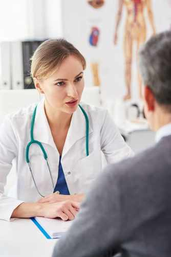 Female doctor talking to her patient in doctor's office