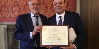"""Nella foto: il presidente dell'AAB Massimo Tedeschi consegna all'ingegner Marco Bonometti la pergamena con il titolo di """"Amico dell'AAB"""", foto da ufficio stampa"""