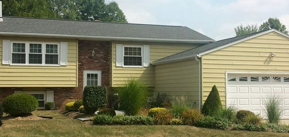picture of a yellow and brick house that just got a fascia installation in medina ohio by brightside home restoration