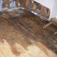 picture of a floor and wall that have been water damaged for water restoration company in medina ohio