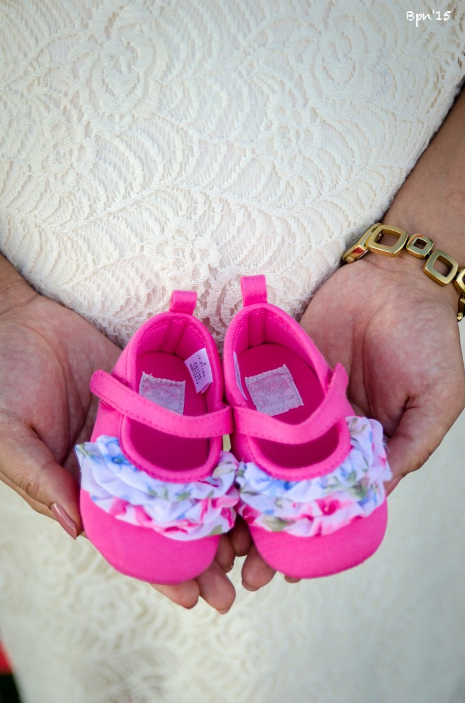 Mom-to-be holding pink girl shoe