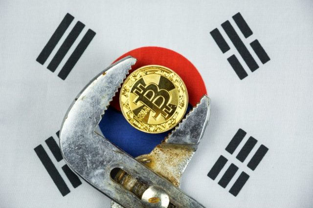 Bitcoin-Münze in Rohrzange vor südkoreanischer Flagge