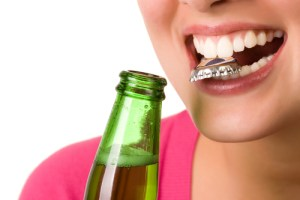 woman opening beer bottle with teeth