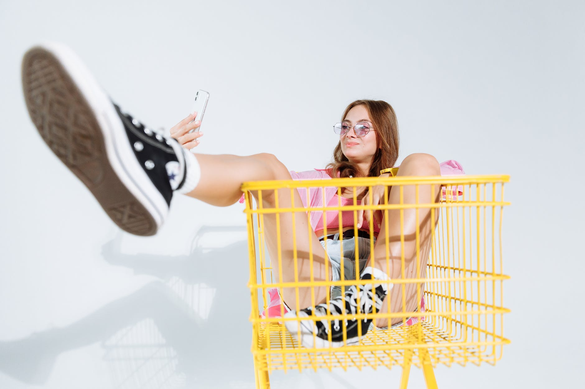 woman in black and white converse all star high top sneakers sitting on yellow shopping cart