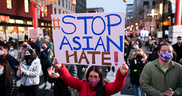 """Photo of a female protestor holding a sign that says """"#Stop Asian Hate!"""" Behind her, the entrance to DC's Chinatown is seen. Protesters rallied to call attention to Asian-American discrimination and remember the Asian-American lives lost in a series of shootings last night in Atlanta, in Chinatown, Washington, D.C., on Wednesday, March 17, 2021."""