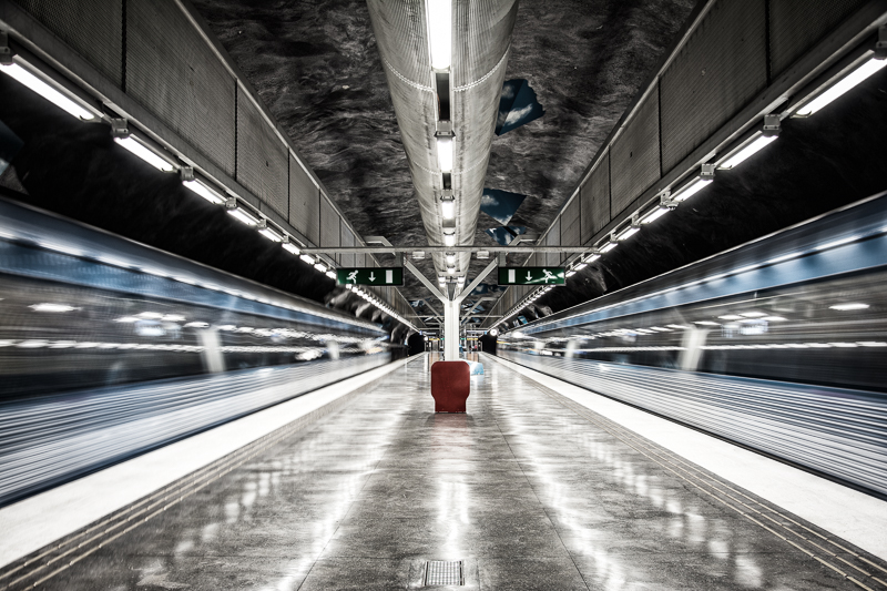 Two moving trains by the platform in the Stockholm subway