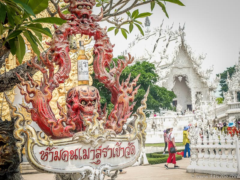 """A sign with a red skull stating that """"alcohol is a sin"""" at White Temple (Wat Rong Khun) in Chiang-Rai"""