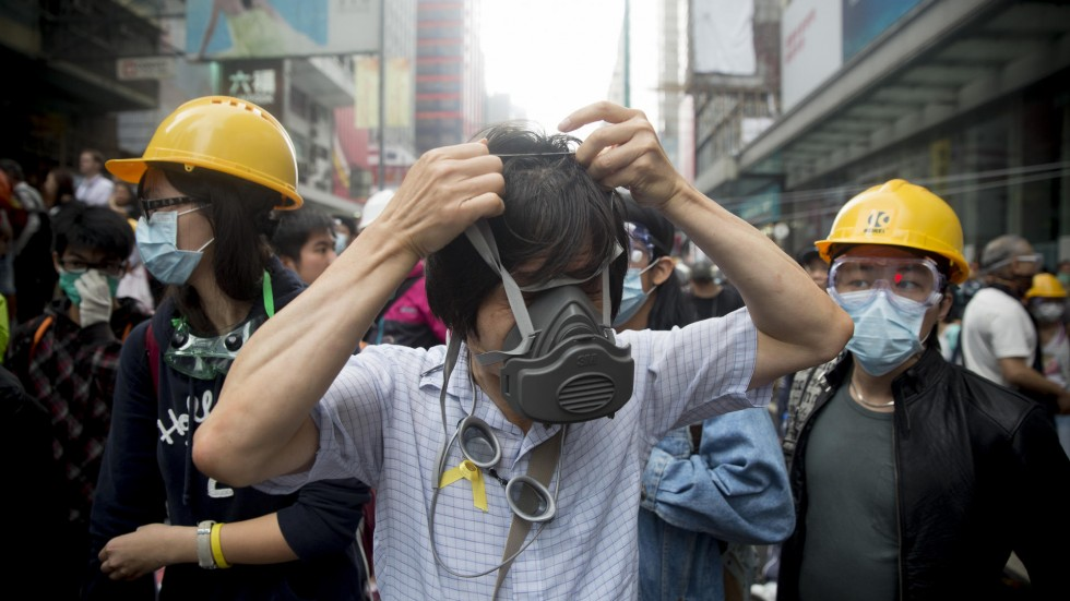 Three people on a busy Beijing street wear masks to aid breathing; two on either side wear fabric surgical masks and hard hats; person in the middle is strapping a large gray plastic breathing mask onto their face.