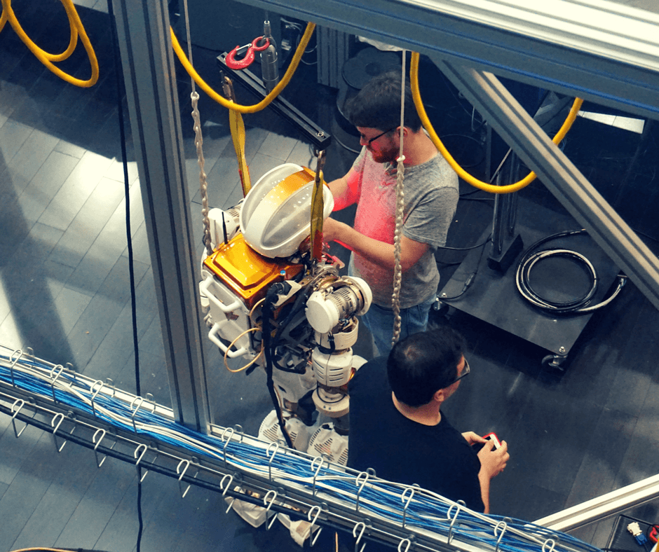 Engineers working on robot inside Building 9 of Space Center Houston
