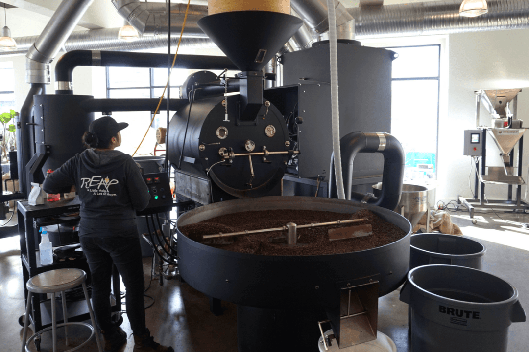 Coffee tumbling out of one of the two San Franciscan drum roasters at Messenger Coffee Co.