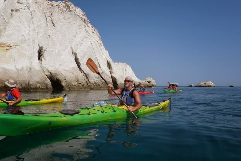 Mark Deaf McGuire in a green kayak with other kayakers paddling along a limestone cliff. Q4