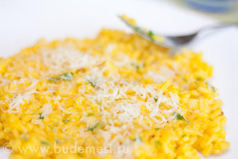 Ризотто с шафраном по-милански ярко желтого цвета посыпанное одной чайной ложечкой мелко натертого твердого сыра