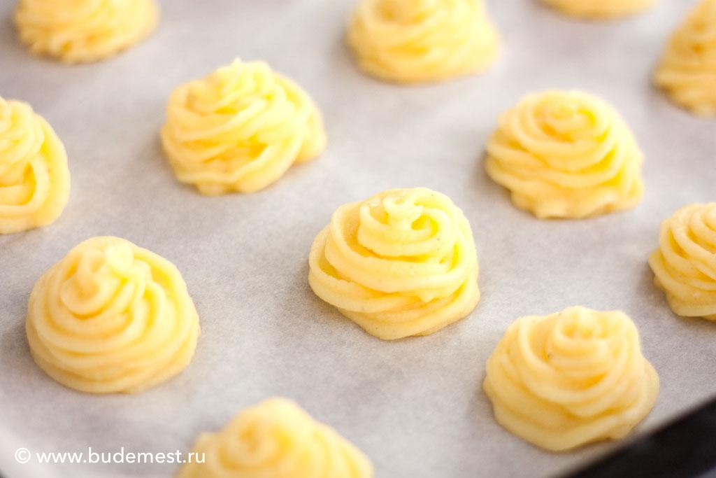 С помощью кондитерского мешка и фигурной насадки формируем горки картофеля на противне