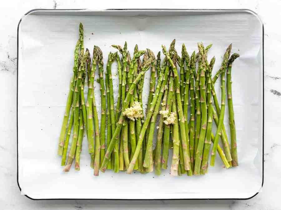 asparagus, garlic, oil, and salt on a baking sheet
