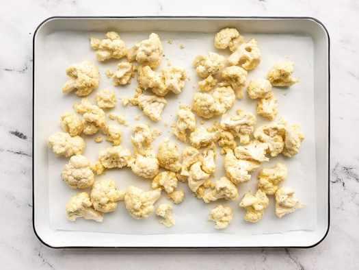 Cauliflower on a lined baking sheet ready to roast
