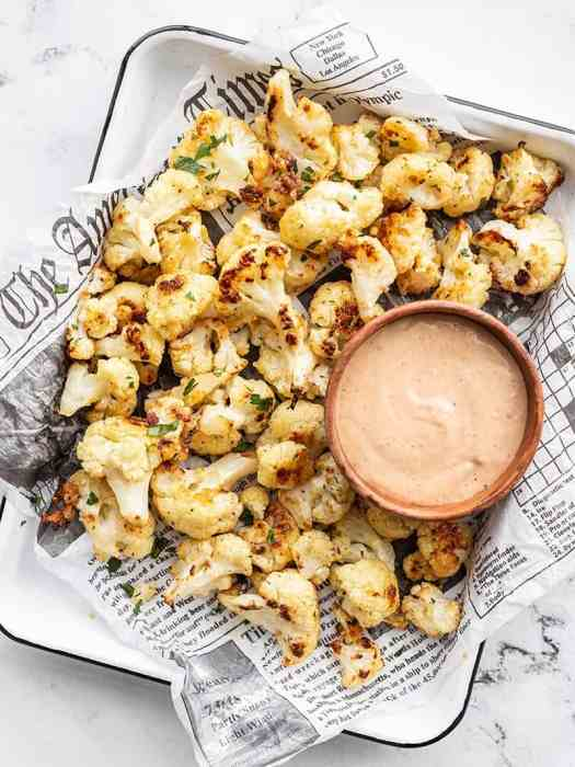 Overhead of Garlic Parmesan Roasted Cauliflower on a tray with a bowl of dipping sauce