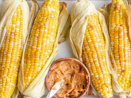 Close up of oven roasted corn with a bowl of honey chili butter
