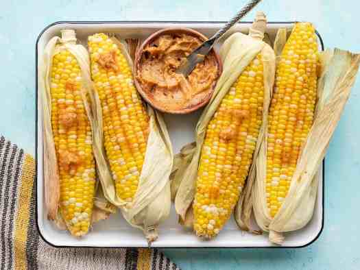 Oven roasted corn on a tray, partially shucked, with a bowl of honey chili butter