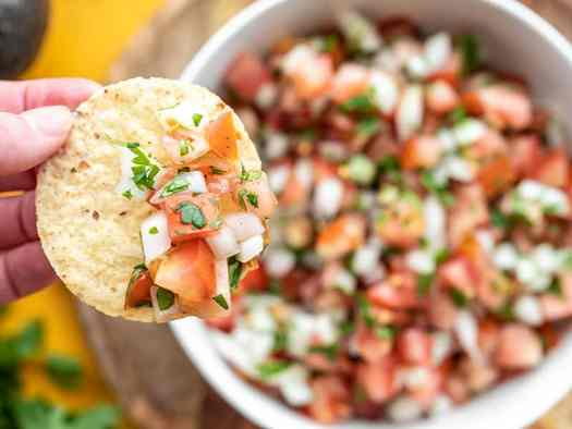 Close up of a chip topped with pico de gallo, the bowl in the background