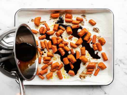honey balsamic glaze being poured over roasted carrots