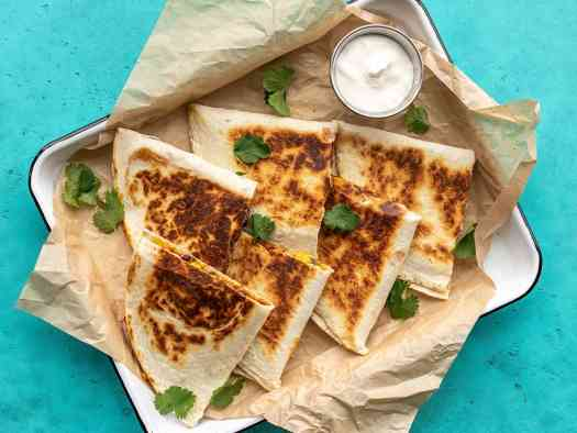 Overhead view of black bean quesadillas on a serving tray with a dish of sour cream