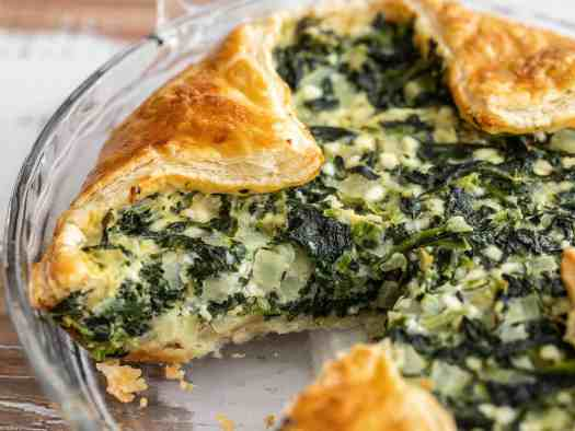 Close up side view of spinach pie in the glass pie dish
