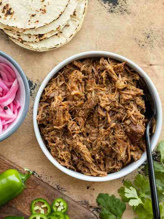 Overhead view of a bowl full of chili rubbed pulled pork with taco fixings on the sides