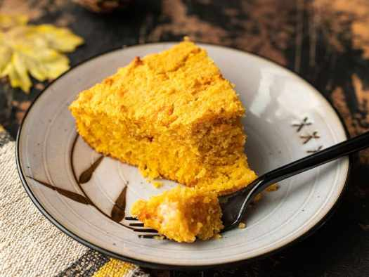 One slice of sweet potato cornbread on a plate with a fork