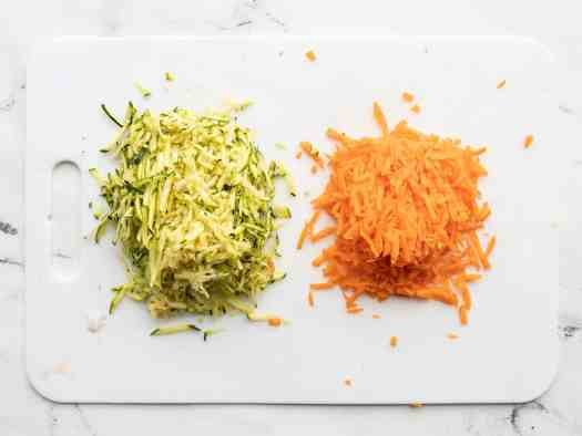 Shredded zucchini and carrot on a cutting board