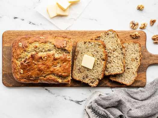 A half sliced loaf of yogurt banana bread on a wooden cutting board with one pat of butter in the center of one slice
