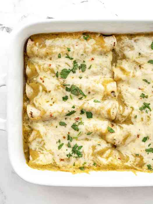 Close up overhead view of green chile chicken enchiladas in a casserole dish