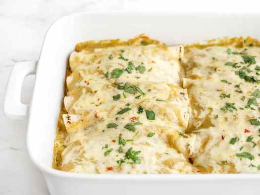 Side view of the casserole dish full of green chile chicken enchiladas