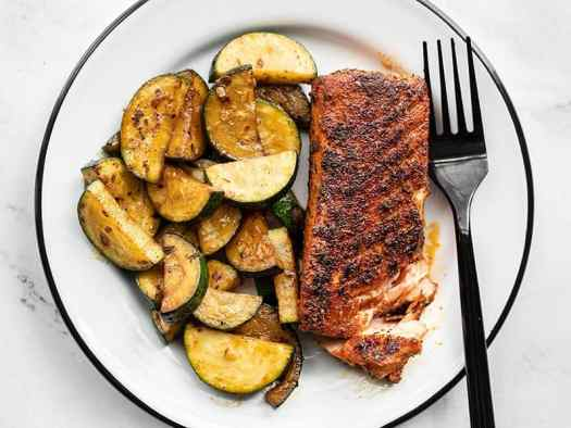 Blackened salmon with zucchini on a plate with a black fork on the side