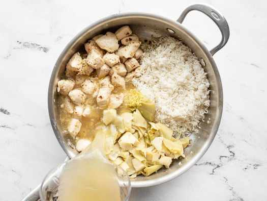 Artichokes, rice, and broth added to the skillet
