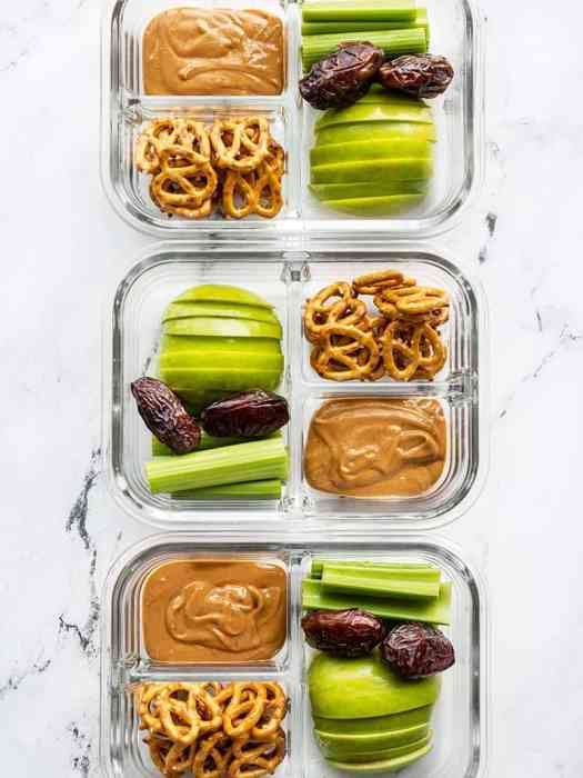 Three glass containers lined up with peanut butter apples, celery, pretzels and dates.