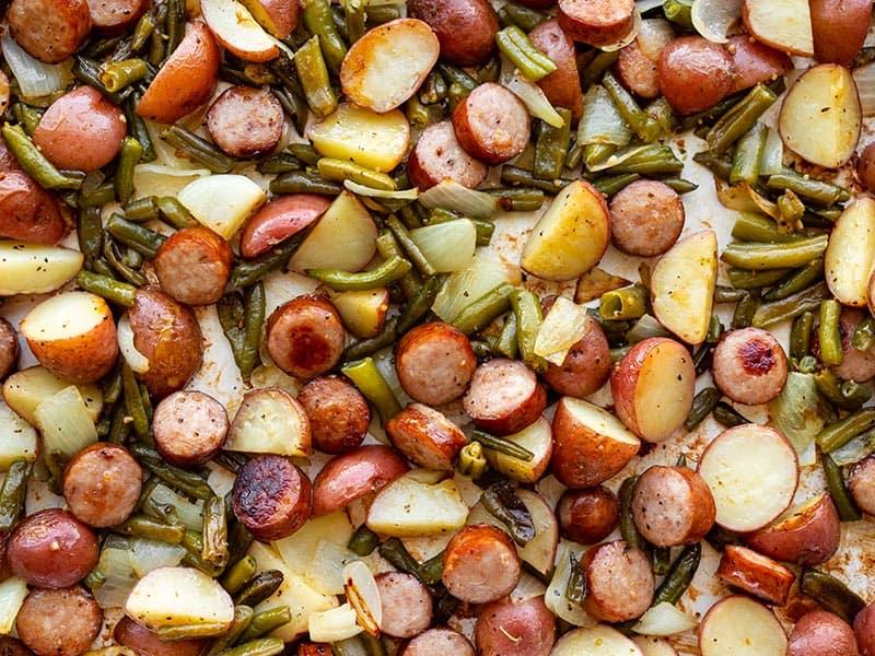 Close up of sheet pan kielbasa potatoes and green beans on a sheet pan