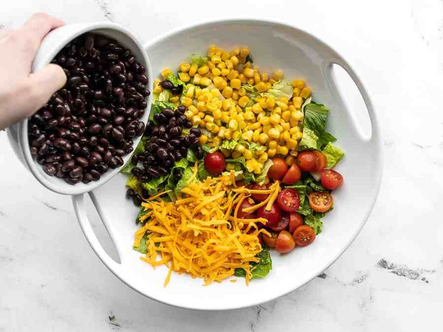 Beans being poured onto the salad with corn, tomatoes, and cheese