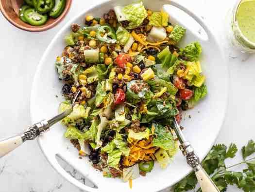 Half-tossed turkey taco salad in a serving bowl with salad tongs