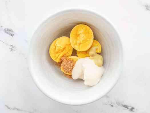 Egg yolks in a bowl with mayonnaise, dijon, and seasoning salt