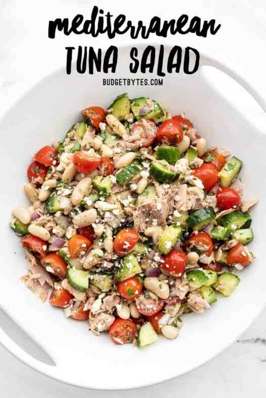 Overhead view of mediterranean tuna salad in a serving dish with title text at the top