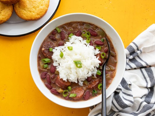 Overhead view of a bowl of quickie red beans and rice with corn muffins on the side