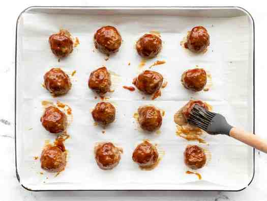 BBQ sauce being brushed onto the meatballs