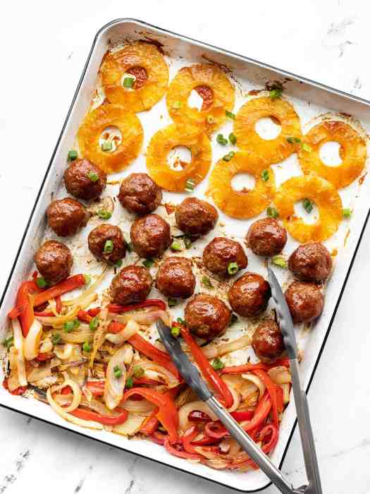 Sheet pan bbq meatballs on the pan with pineapple, peppers, and onions. Tongs resting on the side.