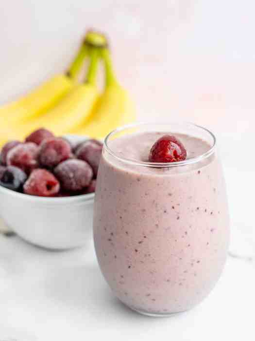 Cherry almond smoothie in a short glass with bananas and a bowl of frozen cherries behind it
