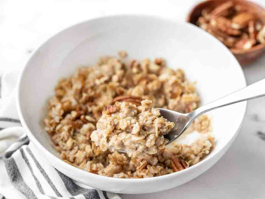 Side view of a spoon lifting a bite of cinnamon pecan cauli oats out of the bowl
