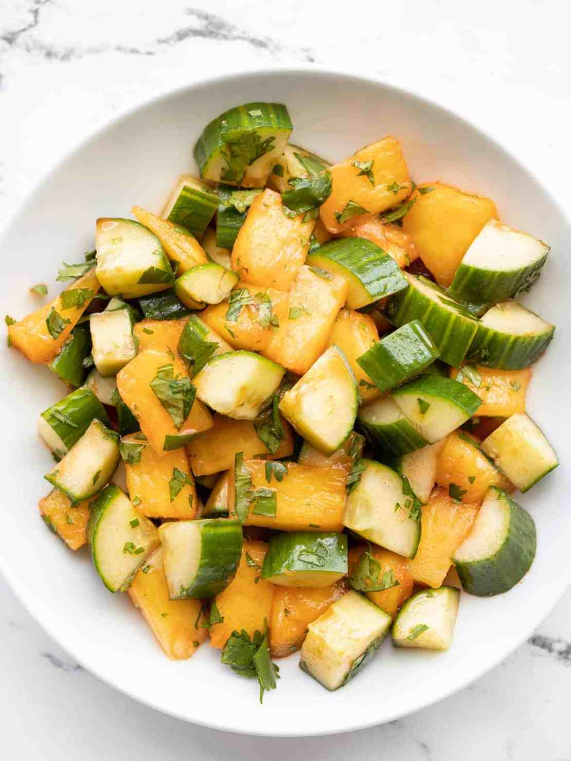 Close up overhead view of a bowl of spicy pineapple cucumber salad