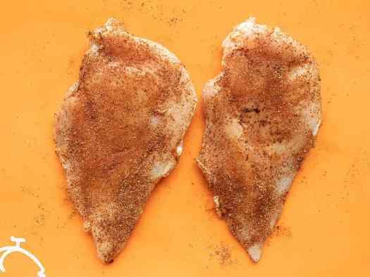 Seasoned chicken breast on an orange cutting board