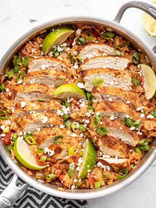 chipotle lime chicken and rice in the skillet, garnished with lime wedges