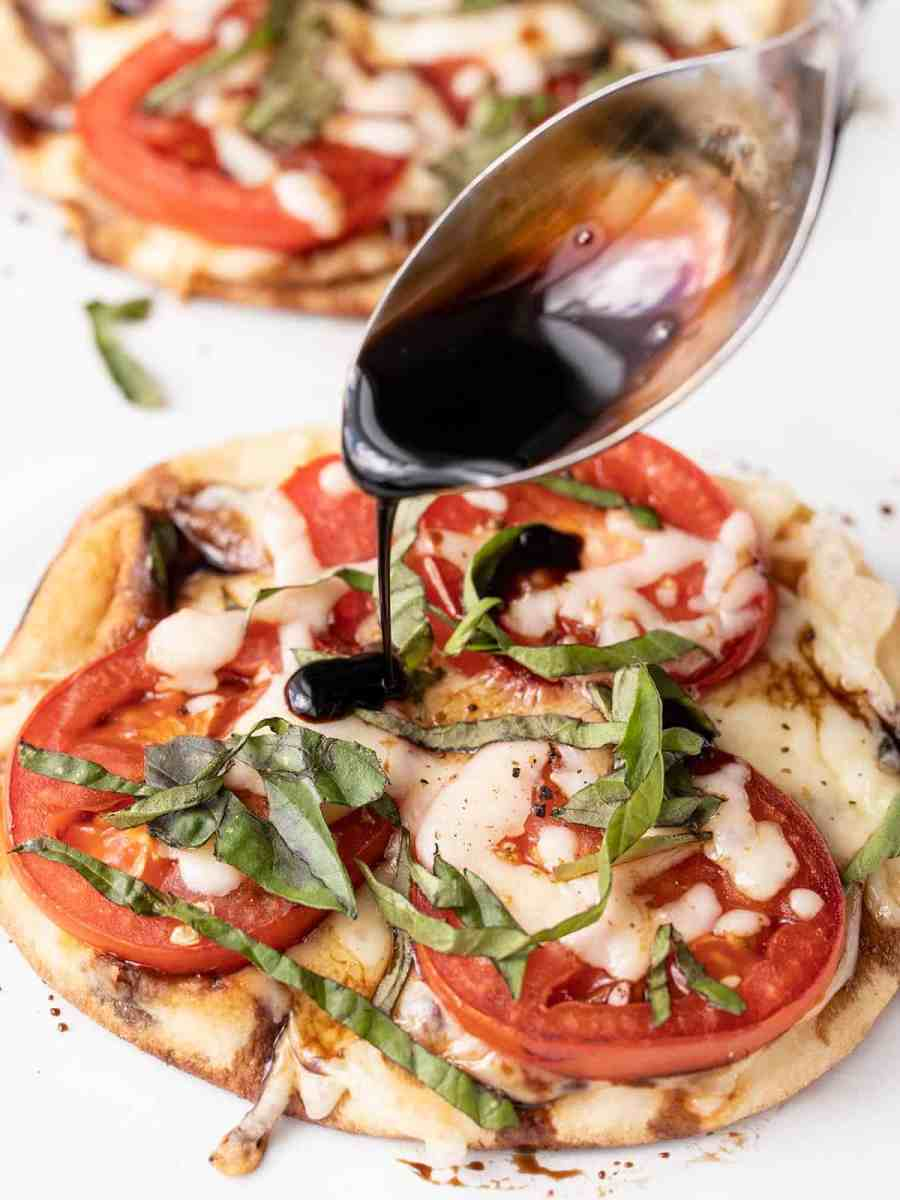 Balsamic reduction being drizzled over the caprese pizza
