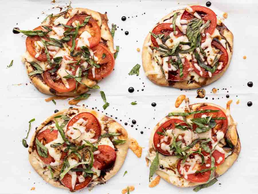 four finished caprese pizzas on a baking sheet
